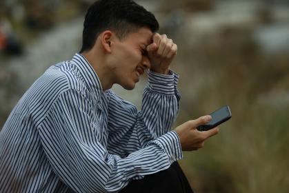 スマートフォンを手に持ち顔を歪める男性