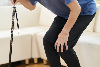膝が痛くて杖をつく高齢者