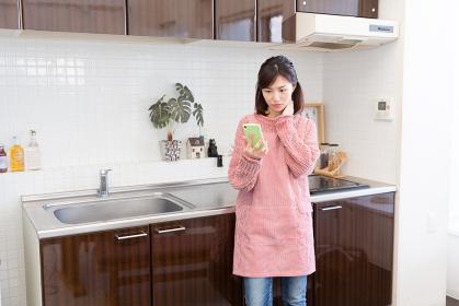 キッチンでスマホを見る女性 考える