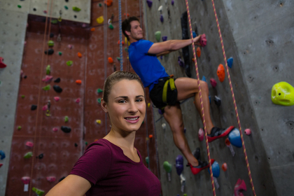 Portrait of female athlete standing against trainer climbing wall