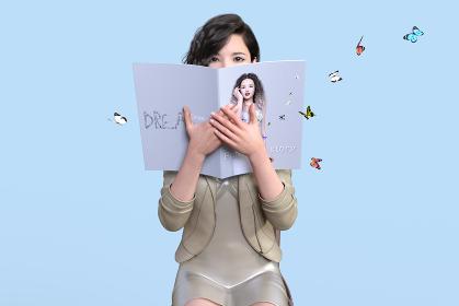 蝶が舞う空間でスーツのビジネス女子が女性が載った雑誌で顔を隠しながら正面を見る