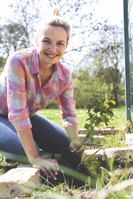young pretty blond woman is preparing vegetables in the garden