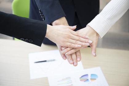 会議室にて3人のビジネスマンが手を合わせる