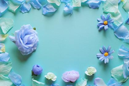 青を基調とした造花と背景。中央空きのコピースペース。花のフレーム。平置きの俯瞰撮影。
