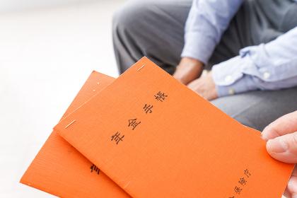 年金手帳を持つ高齢の夫婦
