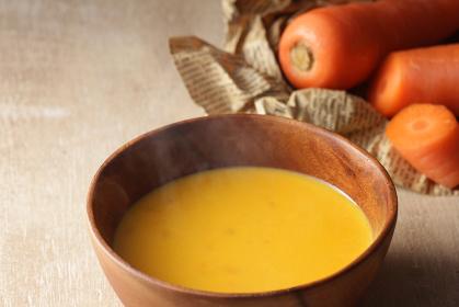 ほかほかの温かい湯気の立つ人参のポタージュスープ
