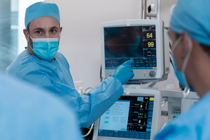 Caucasian male doctor wearing face mask and surgical overalls pointing at monitor. medicine, health and healthcare services during coronavirus covid 19 pandemic.