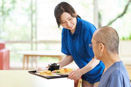 高齢者に配膳をする介護士