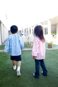 中庭で遊ぶ幼稚園児の後姿