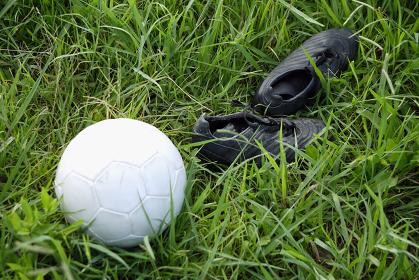 芝生の上にあるサッカーボールとスパイク