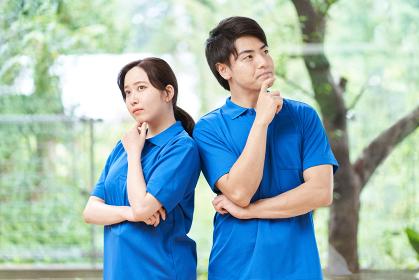 仕事につてい悩む男女の介護士