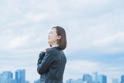 空を見上げるカジュアルな服装のビジネスウーマン