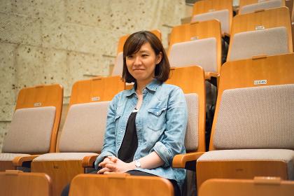 コンサートホールの椅子に座る1人の女性