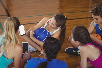 High school girls looking at the mobile phone while relaxing in the basketball court