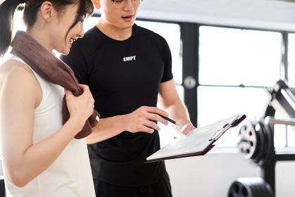 トレーニングのアドバイスをするアジア人男性パーソナルトレーナー