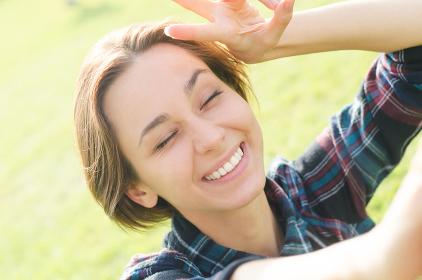 カメラ目線の若い笑顔の女性(セルフショット)