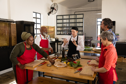 High angle side view of a multi-ethnic group of Senior adults at a cookery class, the diverse adult students listening to instructions from a Caucasian female chef wearing chefs whites and a black hat and apron, standing around a wooden table of ingredients