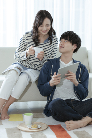 タブレットPCを見るカップル