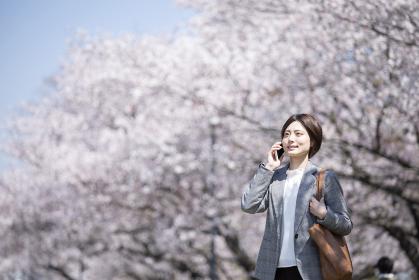 桜とスーツを着た若いビジネスウーマン