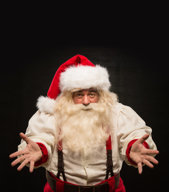 Santa Claus portrait expressing gesturing and presenting something against dark background. Lots of copyspace