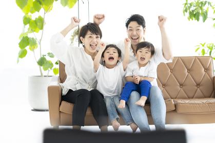 手をあげて喜ぶ親子・テレビ観戦イメージ