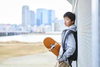 スケボーを持っている日本人中学生