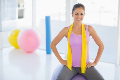 Portrait of happy woman sitting on exercise ball