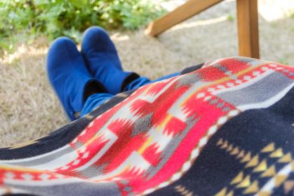 屋外で膝に毛布を掛ける女性 アウトドア バーベキュー テラス席