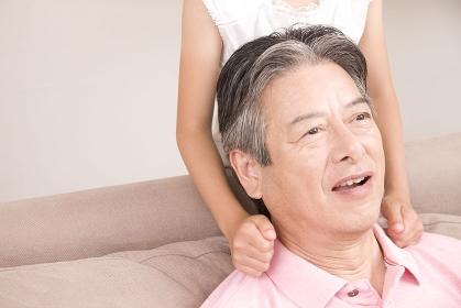 孫娘に肩をたたかれる祖父