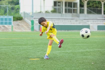 シュートするサッカー少年