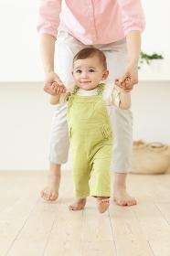 お母さんと歩く練習をする赤ちゃん