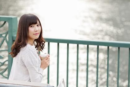 川沿いでホットドリンクを飲む若い日本人女性
