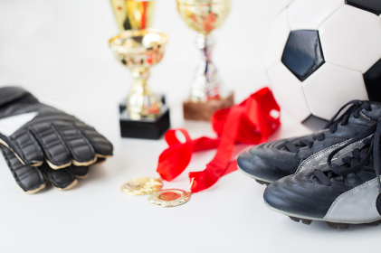 close up of football, boots, gloves, cup and medal