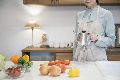 キッチンで調理をする若い女性の手元