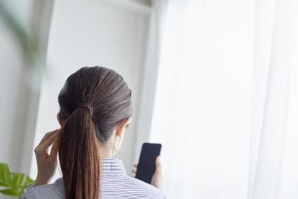 リビングでスマートフォンを操作する若い女性