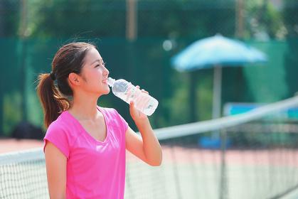 テニスコートで休憩する若い女性