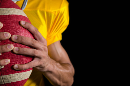 American football player holding a ball with both his hands