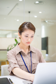 真剣な表情で仕事をする女性(清潔なオフィス)