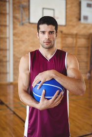 Determined basketball player holding a basketball