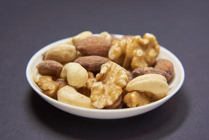 小皿に盛ったミックスナッツ 黒い背景