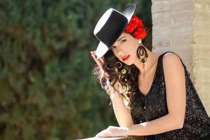 Portrait of beautiful woman, model of fashion, wearing spanish hat and red carnations in her hair
