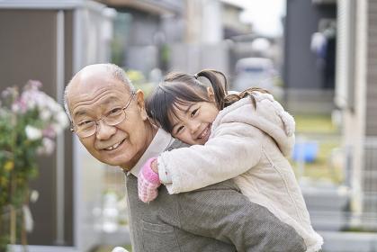 孫をおんぶするシニア男性