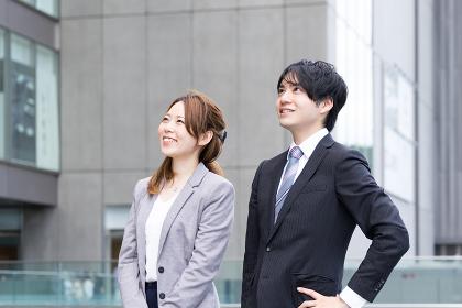空を見上げる男女(ビジネスイメージ)