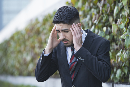 頭痛に悩むビジネスマン