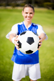 Female football player standing with ball