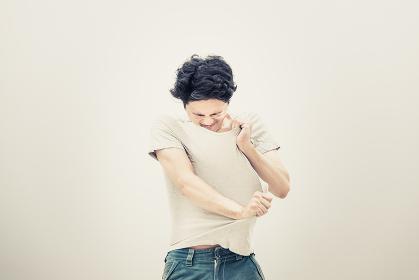 Tシャツを脱ぐ男性(イメージ素材・コンセプト)