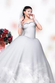 花の置物の前に笑顔ではにかむ純白のウエディングドレスを着た花嫁が立つ