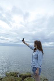 海岸に立ってスマートフォンで自分を撮影する日本人女性