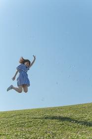 草原をジャンプする日本人女性