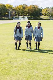 芝生の上を歩く高校生